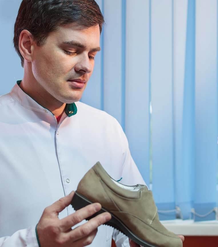 podiatrist holding orthotic footwear